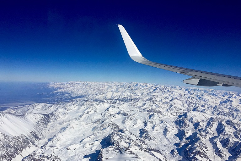 snowy mountains from the window of an airplane