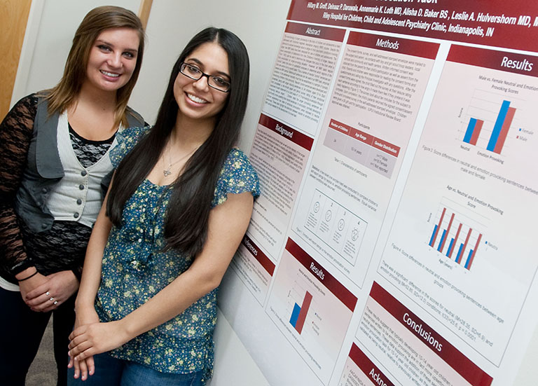 two students with a research poster