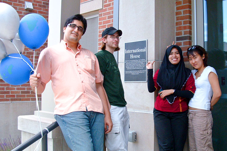 4 students in front of I-House holding international balloons
